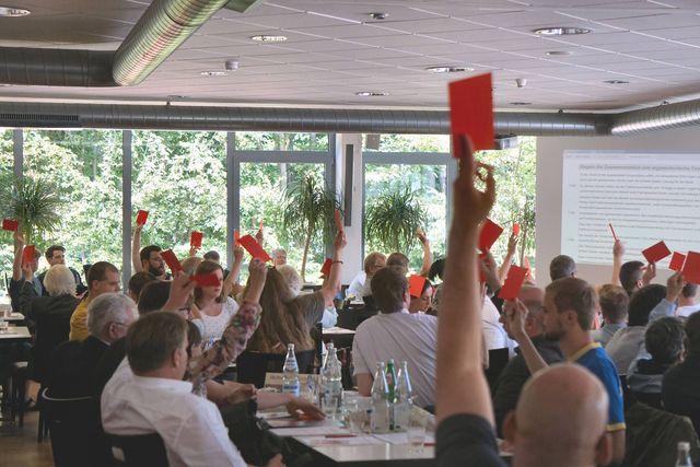 Abstimmung mit roter Stimmkarte. Foto von Wolfram Baumgarten